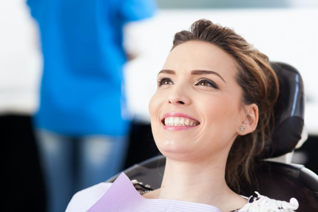 A young lady at the dentist who is about to receive teeth whitening treatment